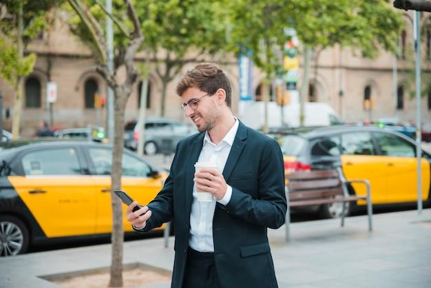 Молодой бизнесмен, держа чашку кофе, глядя на мобильный телефон Бесплатные Фотографии