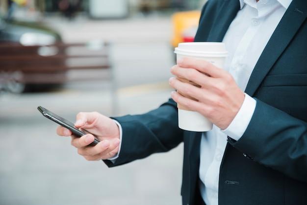 携帯電話を使用してテイクアウトのコーヒーカップを持っているビジネスマンの手のクローズアップ 無料写真