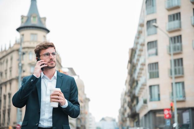 携帯電話で話している手に持ち帰り用のコーヒーカップを持って通りに立っているを保持している実業家 無料写真
