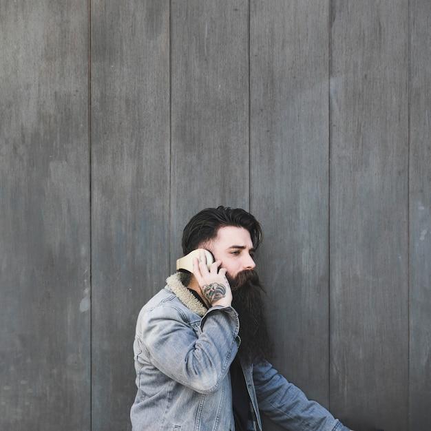 Взгляд со стороны музыки молодого человека слушая на наушниках против серой деревянной стены Бесплатные Фотографии