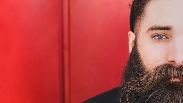 Бородатый молодой человек, глядя на камеру на красном фоне Бесплатные Фотографии