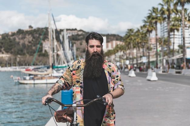 海岸近くの自転車で歩く若い男の肖像 無料写真