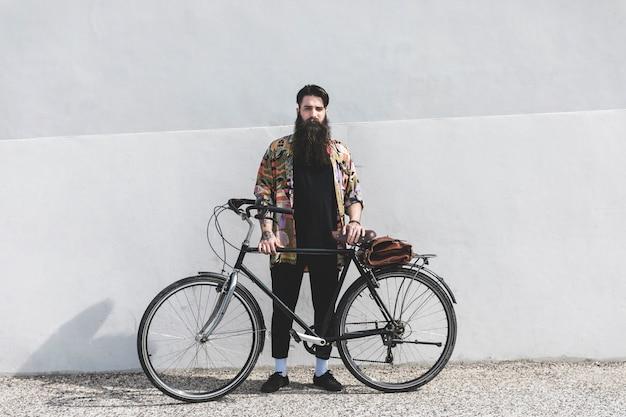 壁に自転車で立っているひげを生やした若い男の肖像 無料写真