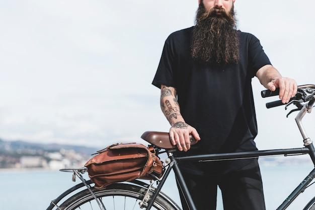 彼の自転車で立っているひげを生やした若い男のクローズアップ 無料写真