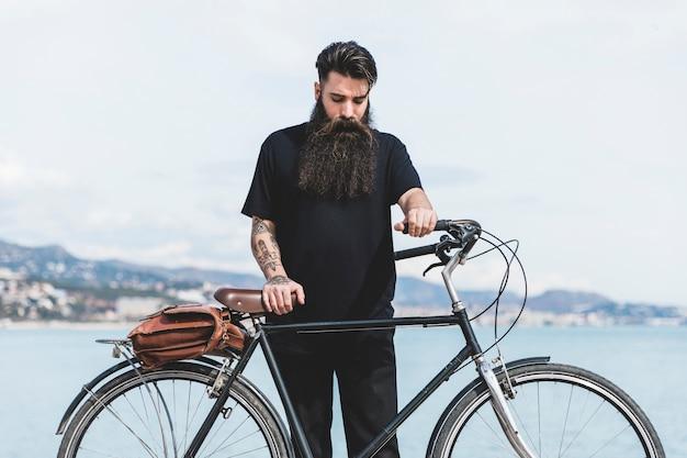 海岸近くに立っている彼の自転車を持つ若い男 無料写真