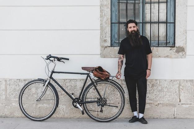 壁にもたれて自転車で立っている人の肖像画 無料写真
