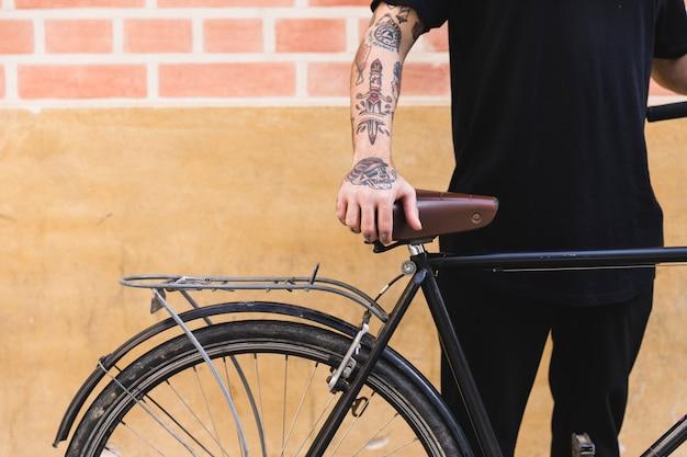 壁の前に自転車で立っている人のクローズアップ 無料写真