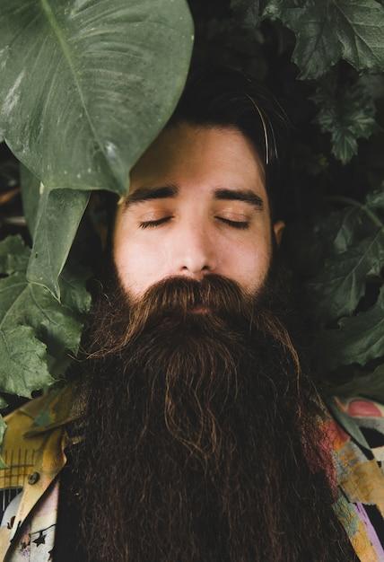 目を閉じてひげを生やした若い男に葉を閉じる 無料写真
