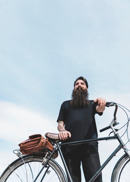 彼の自転車と青い空を背景に立っているひげを生やした男の低角度のビュー 無料写真