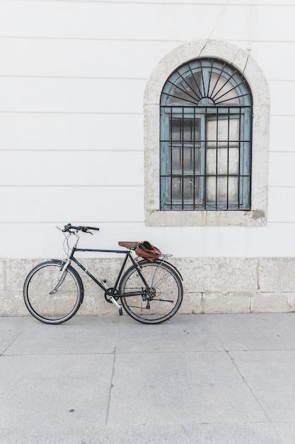 Велосипед припаркован на белой стене с окном Бесплатные Фотографии