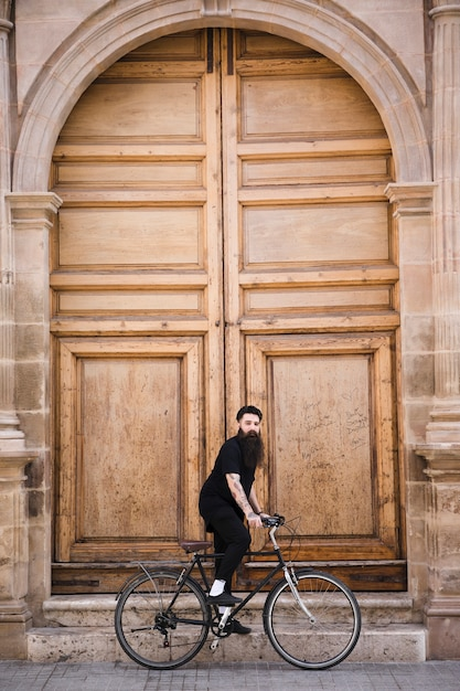 大きな閉じたドアの前で自転車に乗る若い男 無料写真