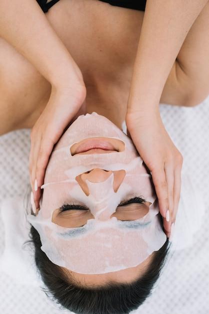 顔のマスクを持つ女性 無料写真