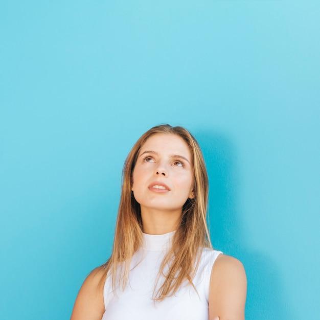 Портрет белокурой молодой женщины смотря вверх против голубой предпосылки Бесплатные Фотографии