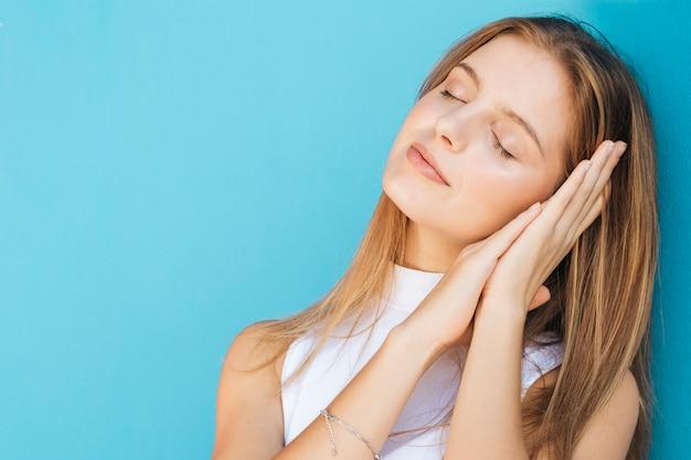 Молодая женщина с закрытыми глазами на синем фоне Бесплатные Фотографии