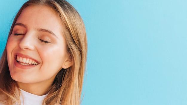 青い背景に対して笑顔の若い女性のクローズアップ 無料写真