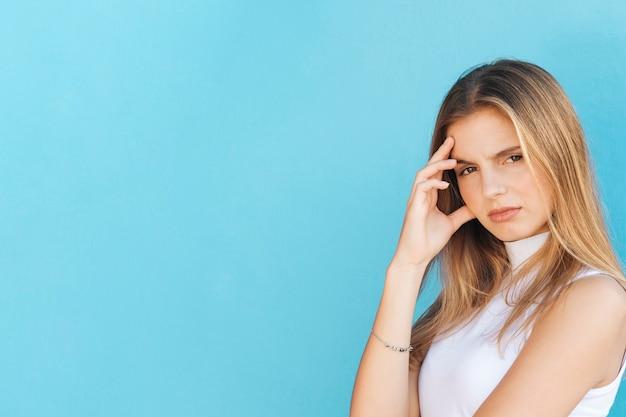 Потревоженная белокурая молодая женщина против голубого фона Бесплатные Фотографии