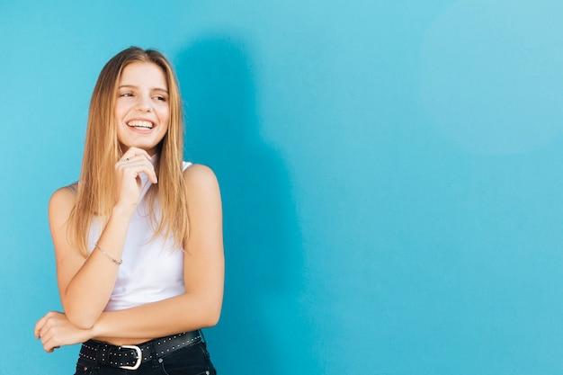 Усмехаясь милая молодая женщина с ее рукой на подбородке смотря камеру против голубой стены Бесплатные Фотографии