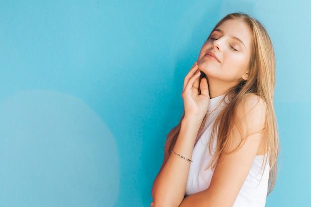 Радует довольно блондинка молодая женщина на синем фоне Бесплатные Фотографии