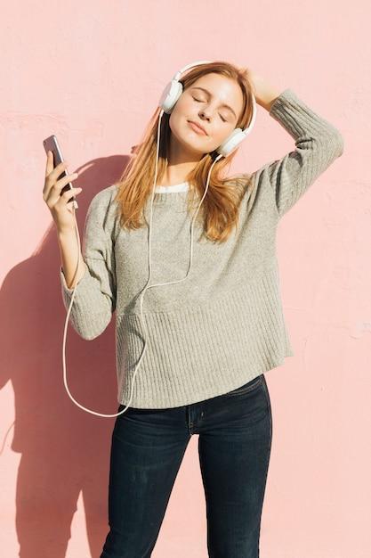 携帯電話で音楽を聴く彼女の頭の上の彼女のヘッドフォンを持つ若い女 無料写真