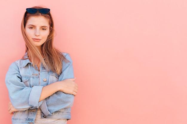 桃の背景に対して立っている魅力的な若い女性 無料写真