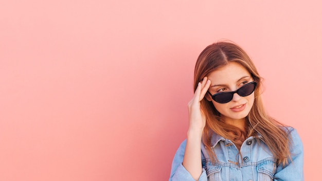 桃の色の背景に対してよそ見サングラスをかけている若い女性を強調します。 無料写真