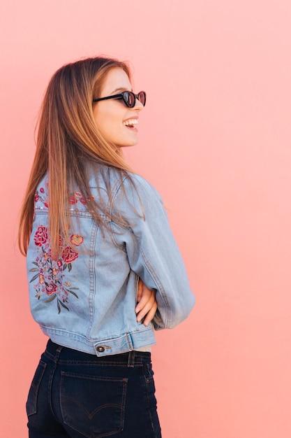 彼女の腕を持つ青いジャケットの若い女性はピンクの背景に対して立っているを渡った 無料写真