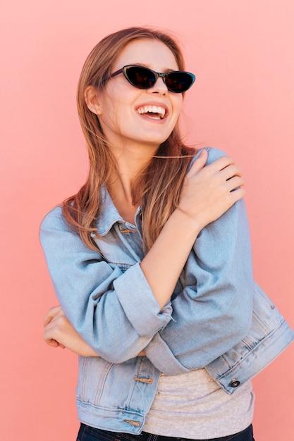 ピンクの背景に対して幸せな金髪の若い女性の肖像画 無料写真