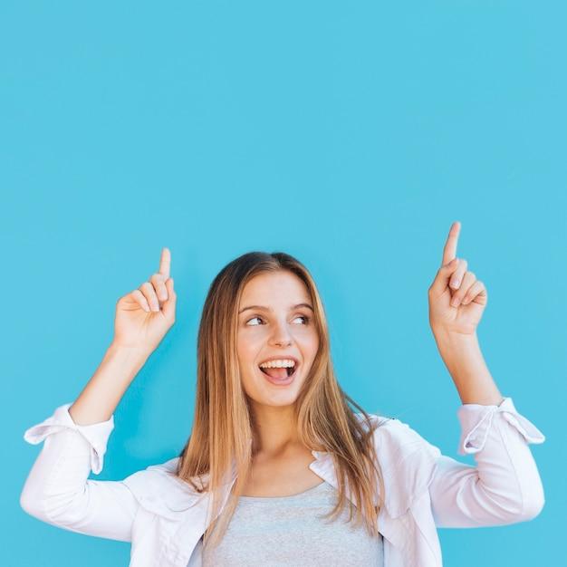 Радостная молодая женщина, указывая пальцем вверх на синем фоне Бесплатные Фотографии