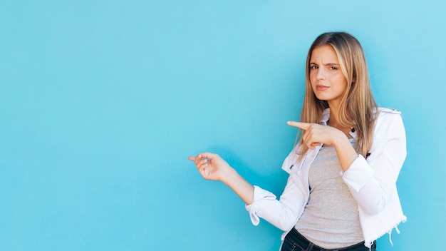 青い背景に対して側に指を指している疑わしいかなり金髪の若い女性 無料写真