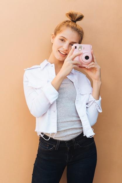 ベージュを背景にピンクのインスタントカメラを持って笑顔の若い女性の肖像画 無料写真