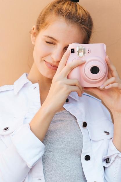 ベージュを背景にピンクのインスタントカメラで画像をクリックする若い女性の肖像画 無料写真