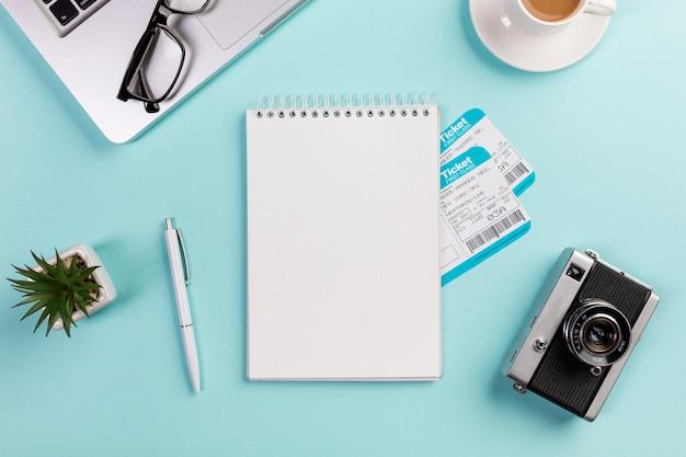 ノートパソコン、眼鏡、ペン、カメラ、青い机の上のコーヒーカップに囲まれた航空券で空白のスパイラルメモ帳 無料写真