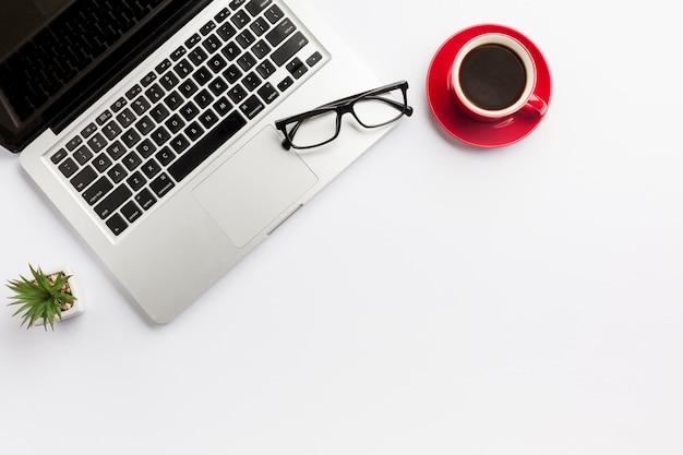 Кактус, чашка кофе и очки на ноутбуке на белом фоне Бесплатные Фотографии