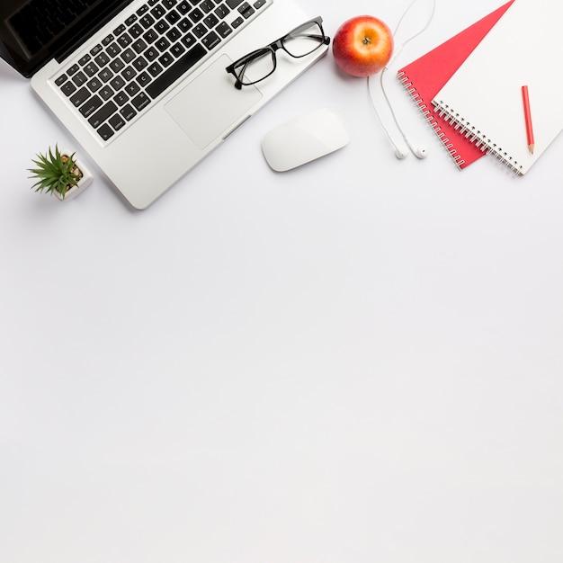 ノートパソコン、眼鏡、マウス、イヤホン、白い背景の上のスパイラルメモ帳とアップルのサボテンの植物 無料写真