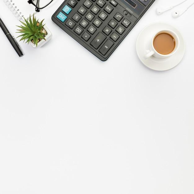 ペン、サボテンの植物、電卓、イヤホン、白い背景の上のコーヒーカップ 無料写真