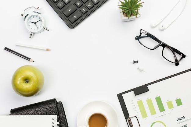 ホワイトオフィスの机の上の文房具とグリーンアップル 無料写真