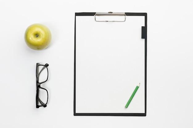 Зеленое яблоко с очками и зеленым карандашом на белом планшете над белым офисным столом Бесплатные Фотографии