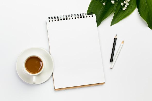 コーヒーカップ、空白のスパイラルメモ帳、葉と事務机の上の花の色鉛筆 無料写真