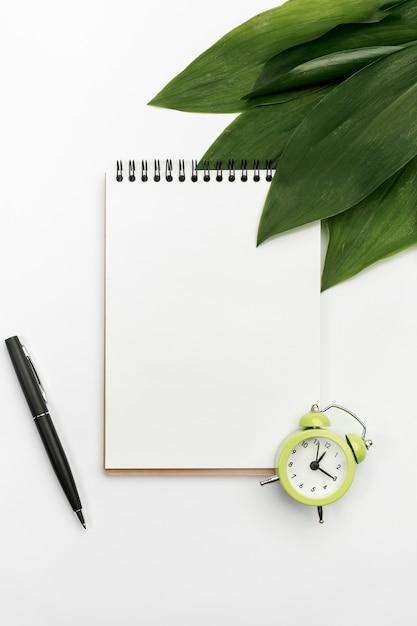 目覚まし時計と白い背景の上のペンとスパイラルメモ帳に緑の葉 無料写真