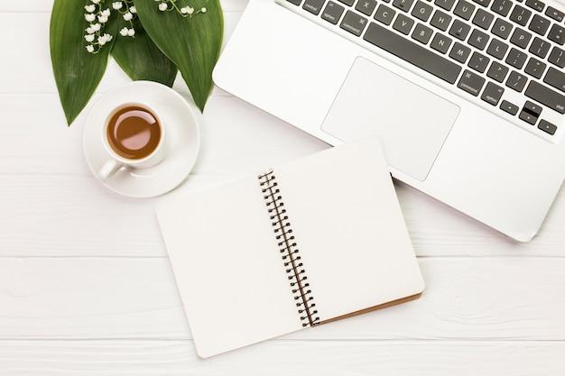 白い木製の机の上のノートパソコンの近くのスパイラルメモ帳とコーヒーカップ 無料写真