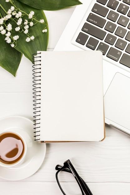 ノートパソコンとコーヒーカップの葉と机の上の花の空白のスパイラルメモ帳 無料写真