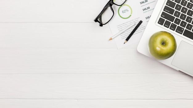 色鉛筆と机の上の予算計画に眼鏡のラップトップ上の青リンゴ 無料写真