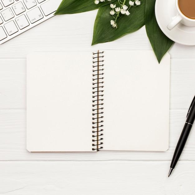 キーボード、コーヒーカップ、白い背景の上にペンを持つ空白のスパイラルメモ帳 無料写真