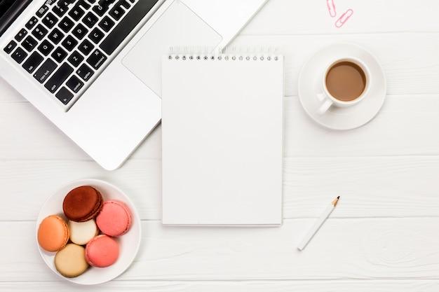 カラフルなマカロンと木製の事務机の上のラップトップ上のスパイラルメモ帳とコーヒーカップ 無料写真