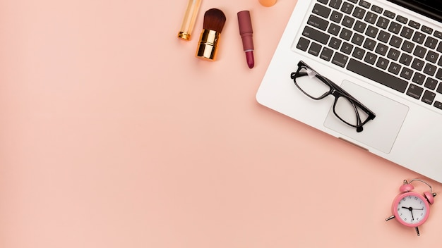 Макияж кисти, помада возле ноутбука с очками и будильником на цветном фоне Бесплатные Фотографии