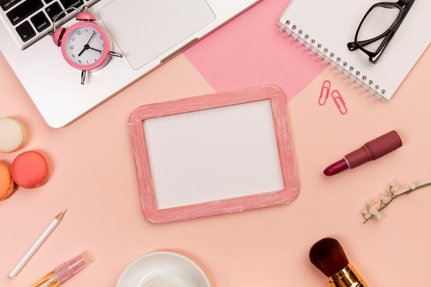色付きの背景に化粧ブラシ、マカロン、ホワイトボードのスレートとラップトップ上の目覚まし時計 無料写真