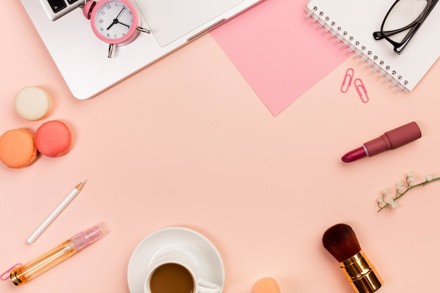 マカロン、コーヒーカップ、化粧筆、目覚まし時計、ピーチ色の背景上のラップトップ 無料写真