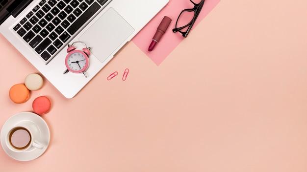 コーヒーカップ、マカロン、目覚まし時計、ノートパソコン、眼鏡、桃の背景に口紅 無料写真