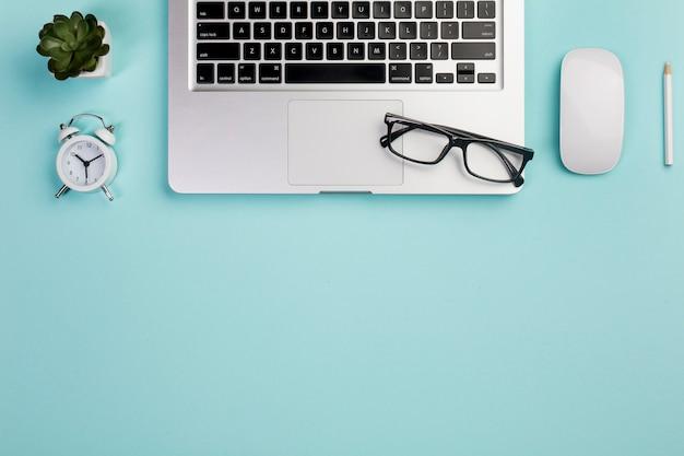 サボテンの植物、目覚まし時計、ノートパソコン、眼鏡、マウス、青い机の上の鉛筆 無料写真