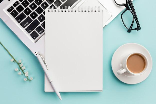 Ручка и спиральный блокнот на ноутбуке с очками, цветочной веточкой и кофейной чашкой на синем офисном столе Бесплатные Фотографии
